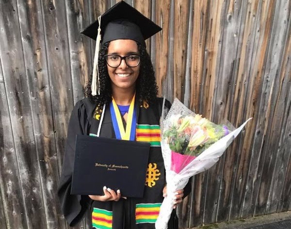 Ariany Pina in a graduation robe and colorful stole, holding flowers and a diploma.