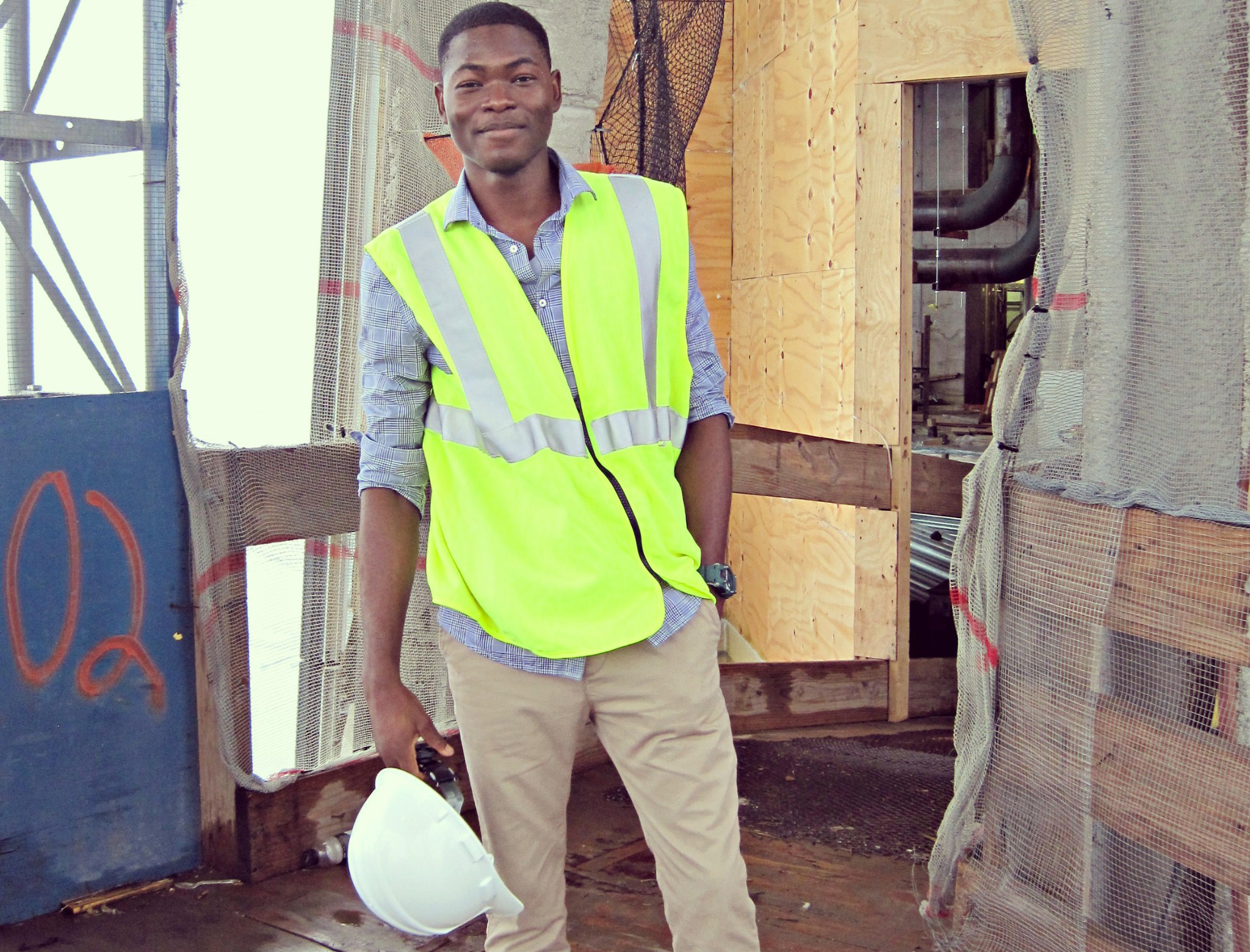 Gideon stands at a construction site in a yellow safety vest, holding a construction helmet in his right hand.