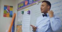 Carlos addresses a classroom