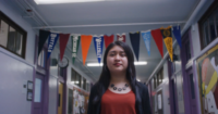 Cinthia Ibarra walks through a school hallway with college banners hanging behind her.