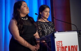 Andrea Magaña and Yessenia Lopez address the audience.