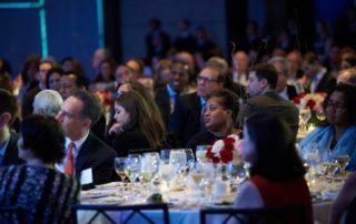 Audience members listening to speakers.