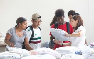 A Grad Bag volunteer helps students pick out bedding.