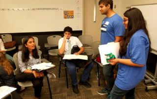 Volunteers talk with students.
