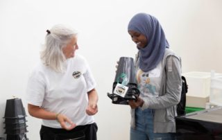 A Grad Bag volunteer recommends an air purifier to a student.