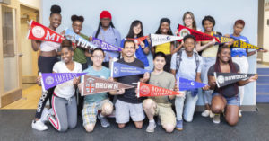 Students pose with their college banners.