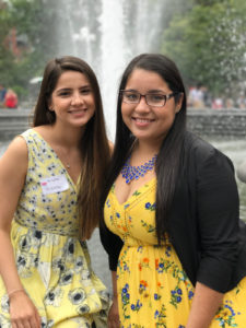 Andrea and Yessenia pose in front of a fountain.